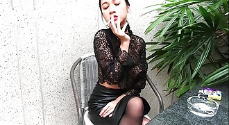 Young lady smokes stripped to the waist and in leather miniskirt